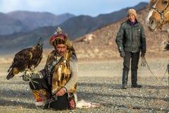 Охотник орла Berkutchi пока охотящся к зайцам с беркуты на его оружиях в горах aimag Bayan-Olgii стоковые изображения rf