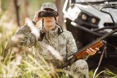Охотник при корокоствольное оружие смотря через бинокли в лесе стоковые изображения rf