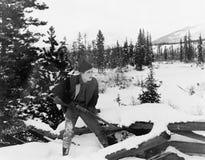 Охотник с его винтовкой идя через снег покрыл сельскую местность (все показанные люди более длинные живущие и никакое имущество н Стоковые Изображения