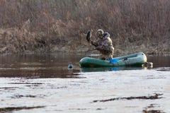 Охотник с заполненными утками на шлюпке Стоковое Фото