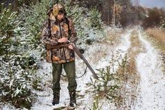 Охотник с рюкзаком и звероловство дают полный газ в лесе зимы Стоковая Фотография