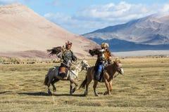 Охотник Berkutchi орла казаха с лошадью учит его дочери к охотиться к зайцам с беркуты Стоковые Фотографии RF