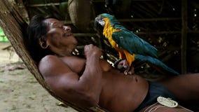 Охотник Huaorani холя его попугая Ara сток-видео