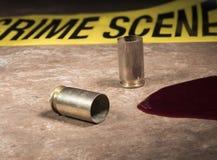 Охраните ленту позади с пустой латунью и кровью пистолета в передней части Стоковые Фотографии RF
