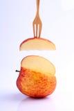Охладите красное яблоко на вилке на белой предпосылке Стоковые Изображения RF