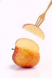 Охладите красное яблоко на вилке на белой предпосылке Стоковое Изображение