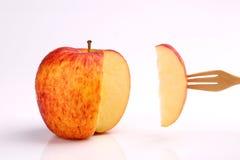 Охладите красное яблоко на вилке на белой предпосылке Стоковое фото RF