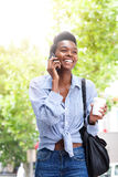 Охладите молодую чернокожую женщину идя и говоря на мобильном телефоне Стоковая Фотография