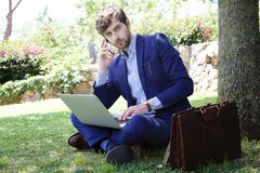 Охладите работая бизнесмена сидя на траве в парке города Стоковые Изображения RF