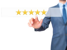 Оценка 5 звезд - кнопка отжимать руки бизнесмена на scr касания Стоковые Фото