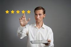Оценка или ранжировка 5 звезд, проверять концепция Человек с ПК таблетки определяет обслуживание, гостиницу, ресторан Стоковое фото RF