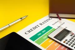 Оценка кредитоспособности на желтой таблице, ручка, калькулятор, тетрадь стоковое фото rf
