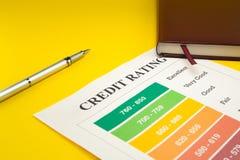 Оценка кредитоспособности на желтой таблице, ручка, тетрадь стоковое изображение