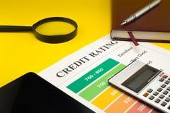 Оценка кредитоспособности на желтой таблице, ручка, увеличитель, тетрадь стоковые фото