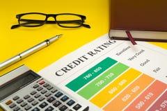 Оценка кредитоспособности на желтых таблице, ручке, стеклах, тетради и калькуляторе стоковая фотография