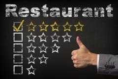 Оценка ресторана 5 пятизвездочная Большие пальцы руки поднимают звезды оценки обслуживания золотые на доске стоковое фото
