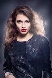 очарование девушки способа красивейшего яркого брюнет темное ее высокие губы смотрит таблицу красного отражения портрета зеркала  Стоковое Изображение RF