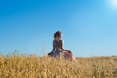 Очаровательная девушка в красивом бежевом платье в рож поля стоковая фотография rf