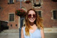 Очаровательная девушка в солнечных очках против фона красивого старого здания Стоковая Фотография RF
