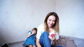 Очаровательная женская и молодая мать говоря на телефоне на предпосылке Стоковое фото RF