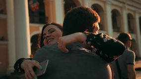 Очаровательная женщина брюнет вызывая smartphone и ходом для того чтобы обнять ее парня на городской улице Город захода солнца акции видеоматериалы