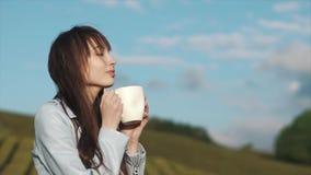 Очаровательная женщина выпивает чай от большой белой чашки стоя на плантации чая видеоматериал
