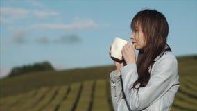 Очаровательная женщина выпивает чай от большой белой чашки стоя на плантации чая акции видеоматериалы