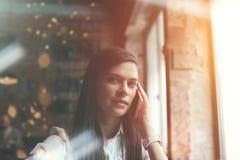 Очаровательная женщина говоря на телефоне в кафе Яркое солнечное утро в кафе Стоковые Изображения RF