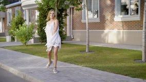 Очаровательная жизнерадостная женщина в вскользь платье идя вдоль тротуара и смотря камеру акции видеоматериалы