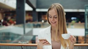 Очаровательная молодая женщина держит smartphone в одной руке и чашке кофе в другом усаживании в кафе видеоматериал