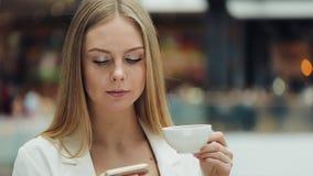 Очаровательная молодая женщина держит smartphone в одной руке и чашке кофе в другом усаживании в кафе сток-видео