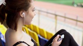 Очаровательная молодая женщина слушает к музыке на стадионе сток-видео