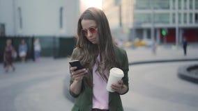 Очаровательная молодая женщина с кофе, который нужно пойти использовать ее smartphone акции видеоматериалы