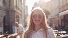 Очаровательная молодая женщина с пышными коричневыми волосами и стильными солнечными очками Привлекательная молодая дама спешит в сток-видео