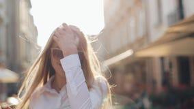 Очаровательная молодая женщина с пышными коричневыми волосами и стильными солнечными очками Привлекательная молодая дама спешит в видеоматериал