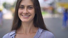 Очаровательная молодая женщина усмехаясь с зубами и смотря в камеру, стоя на городской улице, дневное время сток-видео