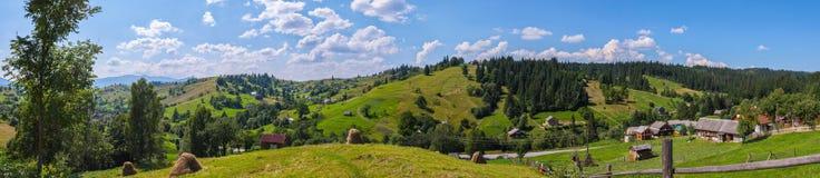 Очаровательная панорама гористых зеленых наклонов на летний день с сельскими домами разбросала вокруг страны с сухим Стоковое Изображение