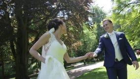 Очаровательные молодые пары новобрачных имеют потеху во время прогулки в солнечном парке весны видеоматериал