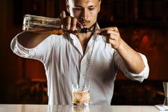 Очаровательный бармен элегантно подготавливает смешанное питье путем лить все стоковые изображения rf