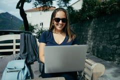 Очаровательный дизайнер женщины в солнечных очках работая с компьтер-книжкой внутри вне Стоковое Фото