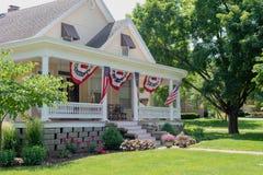 Очаровательный дом украшенный с американскими флагами для четверти Ju стоковое изображение