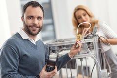 Очаровательный инженер усмехаясь пока заменяющ нить стоковые изображения