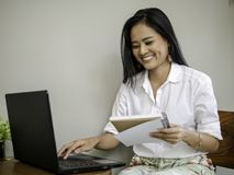 Очаровательный красивый фрилансер в кофейне держа книгу в руке, печатая на клавиатуре компьтер-книжки с усмехаясь стороной стоковое изображение