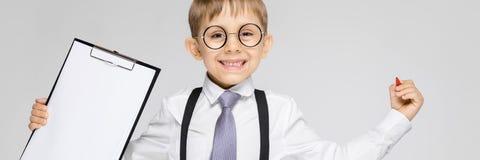 Очаровательный мальчик в белой рубашке, подтяжках, связи и джинсах света стоит на серой предпосылке Мальчик держит ручку и стоковые фотографии rf