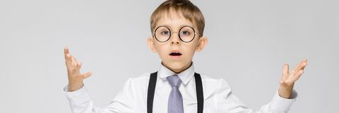 Очаровательный мальчик в белой рубашке, подтяжках, связи и джинсах света стоит на серой предпосылке Мальчик распространил его рук стоковое изображение rf