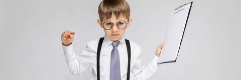 Очаровательный мальчик в белой рубашке, подтяжках, связи и джинсах света стоит на серой предпосылке Мальчик держит ручку и стоковая фотография