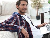 Очаровательный молодой человек при компьтер-книжка сидя в современной живущей комнате стоковое фото