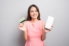 Очаровательная азиатская рука женщины держа smartphone и выставка кредитуют автомобиль стоковое изображение rf