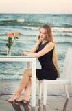 Очаровательная белокурая девушка в модном и черном платье на предпосылке моря Милая молодая дама на предпосылке моря Стоковые Изображения RF