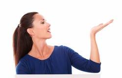 Очаровательная девушка в голубой рубашке держа левую ладонь вверх Стоковые Фотографии RF